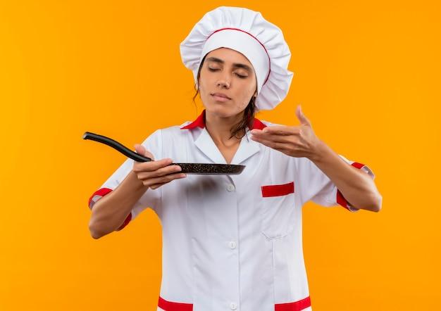 Mit geschlossenen augen junge köchin in kochuniform, die hält und vorgibt, pfanne zu riechen