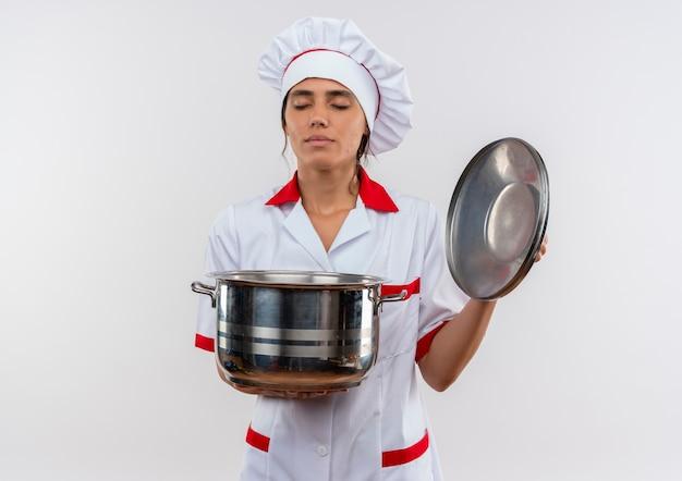 Mit geschlossenen augen junge köchin in kochuniform mit topf und deckel mit kopierraum