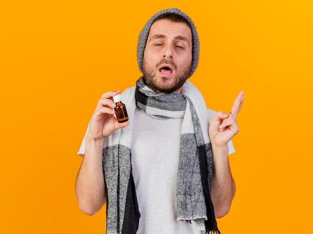 Mit geschlossenen augen junger kranker mann, der wintermütze und schal hält medizin in der glasflasche lokalisiert auf gelbem hintergrund