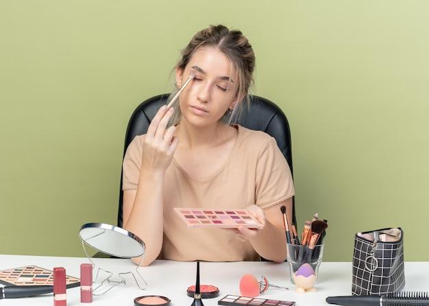 Mit geschlossenen augen junges schönes mädchen sitzt am schreibtisch mit make-up-tools, die lidschatten mit make-up-pinsel auf olivgrünem hintergrund auftragen