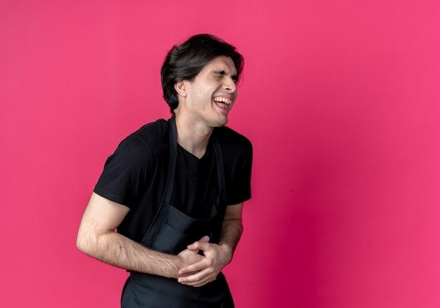 Mit geschlossenen augen lachte der junge hübsche männliche friseur in uniform den auf rosa isolierten bauch