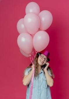 Mit geschlossenen augen lächelndes junges mädchen mit brille und rosa hut, das luftballons hält und am telefon spricht