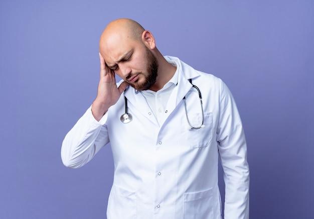 Mit geschlossenen augen müde junge kahle männliche arzt in medizinischen gewand