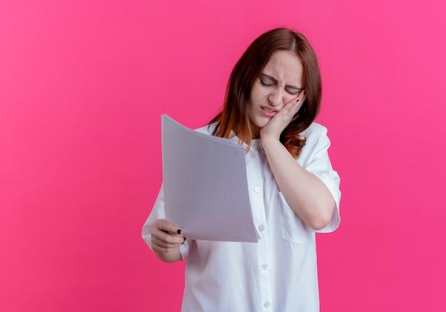 Mit geschlossenen augen müde junges rothaariges mädchen, das papier hält und hand auf wange lokalisiert auf rosa mit kopienraum legt