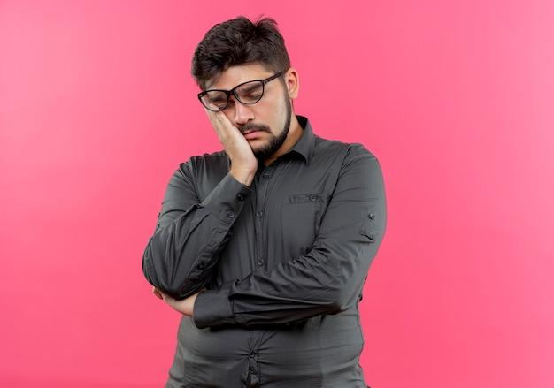 Mit geschlossenen augen müder junger geschäftsmann, der brille trägt, die hand auf wange lokalisiert auf rosa hält