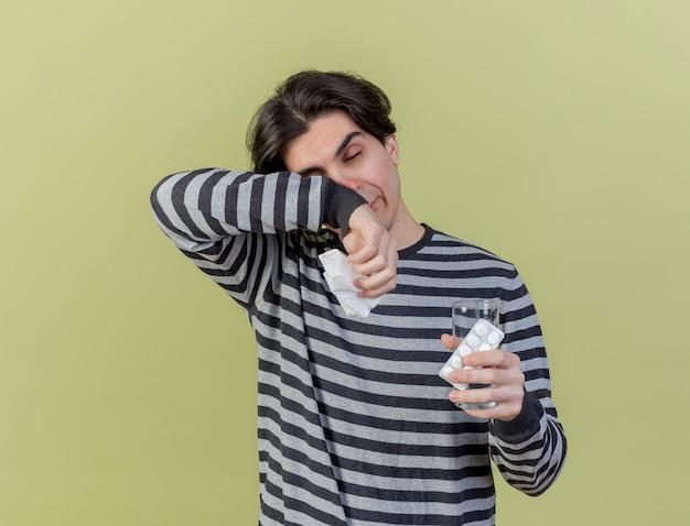 Mit geschlossenen augen schwacher junger kranker mann, der glas wasser mit pillen und wischgesicht mit arm lokalisiert auf olivgrünem hintergrund hält