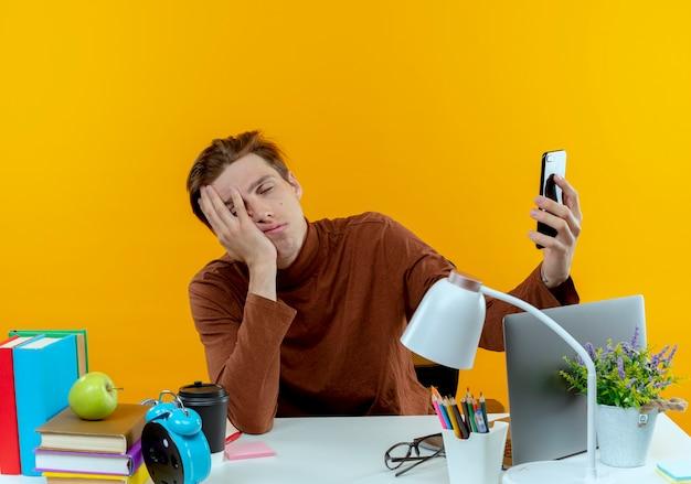 Mit geschlossenen augen sitzen müde junge student junge am schreibtisch mit schulwerkzeugen, die telefon und bedecktes gesicht auf gelb halten