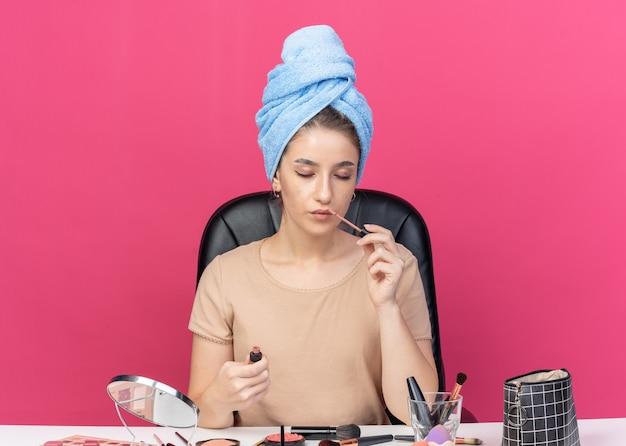 Mit geschlossenen augen sitzt ein junges schönes mädchen am tisch mit make-up-tools, die haare in ein handtuch gewickelt haben und lipgloss auf rosafarbenem hintergrund auftragen