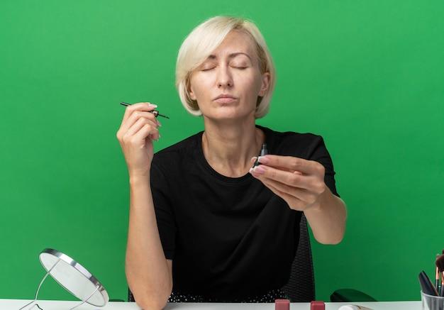 Mit geschlossenen augen sitzt ein junges, schönes mädchen am tisch mit make-up-tools, die wimperntusche in die kamera halten, isoliert auf grünem hintergrund