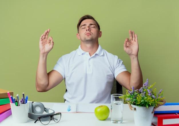 Mit geschlossenen augen sitzt junger hübscher männlicher student am schreibtisch mit schulwerkzeugen, die meditationsgeste lokalisiert auf olivgrün zeigen