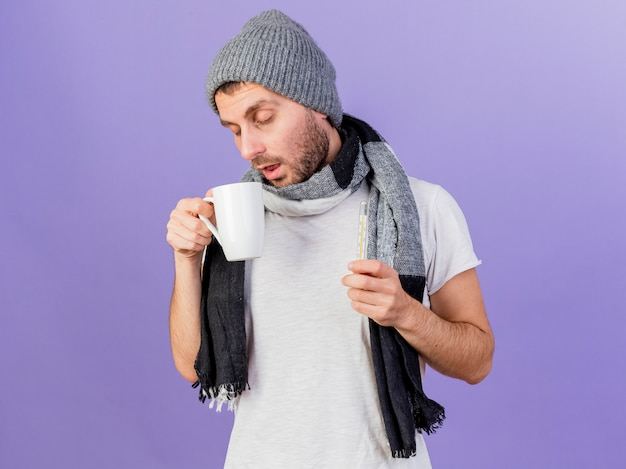 Mit geschlossenen augen trägt der junge kranke mann wintermütze mit schal, der tasse tee und thermometer hält, lokalisiert auf lila hintergrund