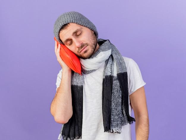 Mit geschlossenen augen trägt der junge kranke mann wintermütze mit schal, der wärmflasche auf wange hält, lokalisiert auf lila hintergrund