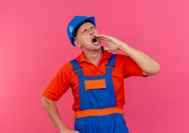 Mit geschlossenen augen trägt der junge männliche baumeister uniform und schutzhelm und ruft jemanden auf rosa an