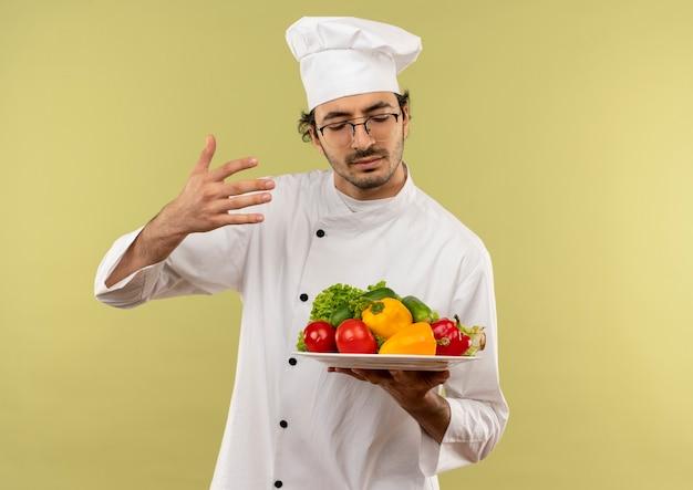 Mit geschlossenen augen trägt der junge männliche koch die kochuniform und die gläser, die gemüse auf teller halten und schnüffeln, isoliert auf grüner wand