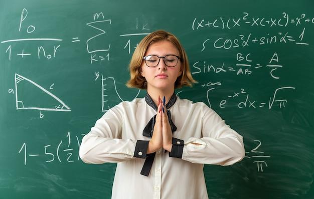 Mit geschlossenen augen trägt eine junge lehrerin eine brille, die vor der tafel steht und eine gebetsgeste im klassenzimmer zeigt