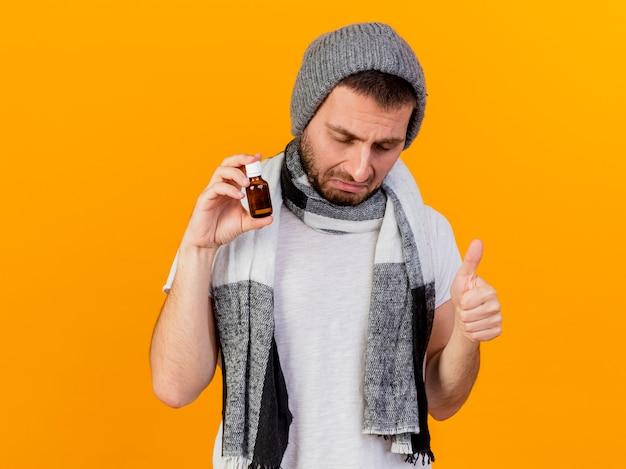 Mit geschlossenen augen trauriger junger kranker mann, der wintermütze und schal hält medizin in der glasflasche zeigt daumen oben isoliert auf gelbem hintergrund