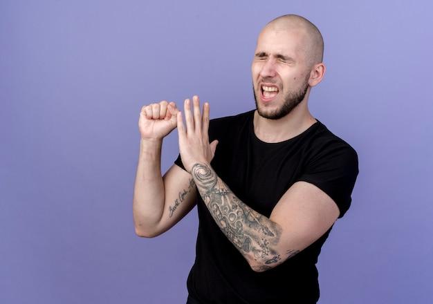 Mit geschlossenen augen unzufrieden jungen sportlichen mann zeigt verschiedene gesten auf lila isoliert