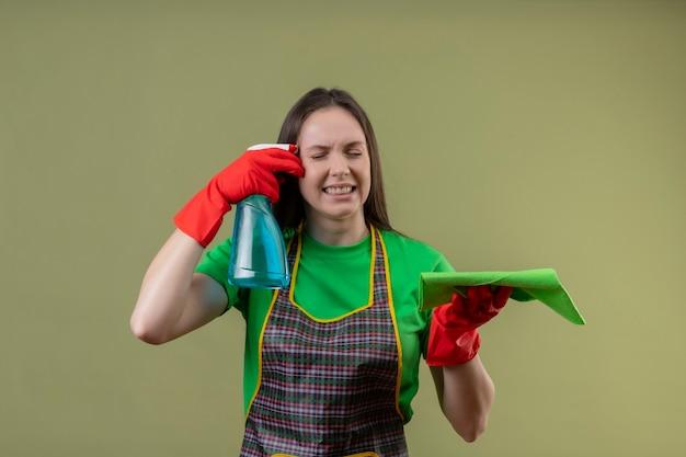 Mit geschlossenen augen unzufrieden reinigung junges mädchen in uniform in roten handschuhen halten reinigungsspray mit lappen und kratzer wange auf isolierten grünen wand