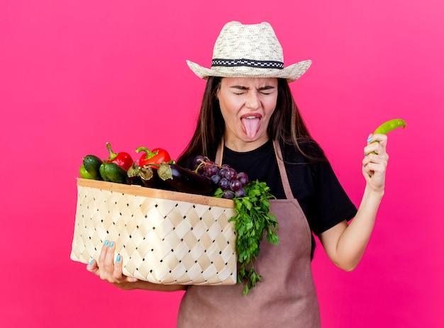 Mit geschlossenen augen unzufriedenes schönes gärtnermädchen in der uniform, die gartenhut hält, der gemüsekorb mit pfeffer zeigt, der zunge lokalisiert auf rosa hintergrund zeigt