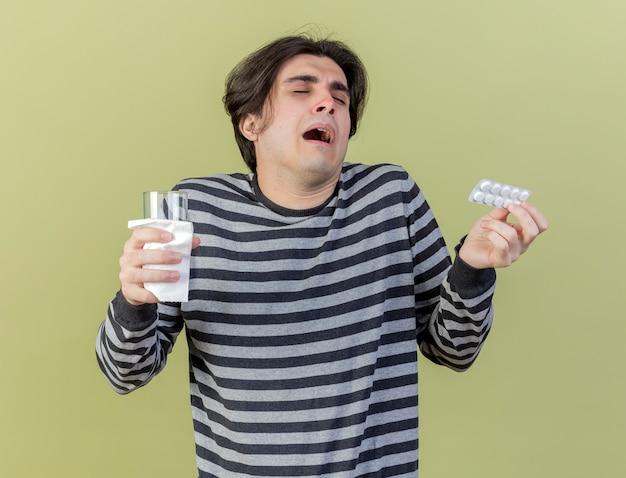 Mit geschlossenen augen verwirrte junger kranker mann, der pillen und glas wasser lokalisiert auf olivgrünem hintergrund hält