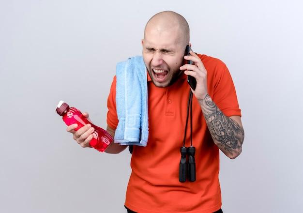 Mit geschlossenen augen wütenden jungen sportlichen mann, der wasserflasche mit handtuch auf schulter mit springseil hält und am telefon lokalisiert auf weißer wand spricht