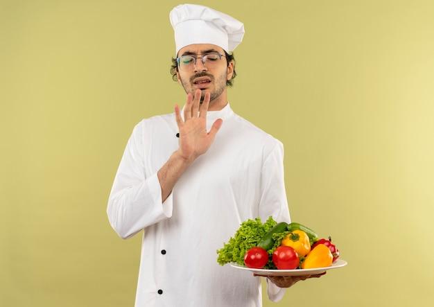 Mit geschlossenen augen zimperlicher junger männlicher koch, der kochuniform und gläser hält, die gemüse auf teller lokalisiert auf grüner wand halten