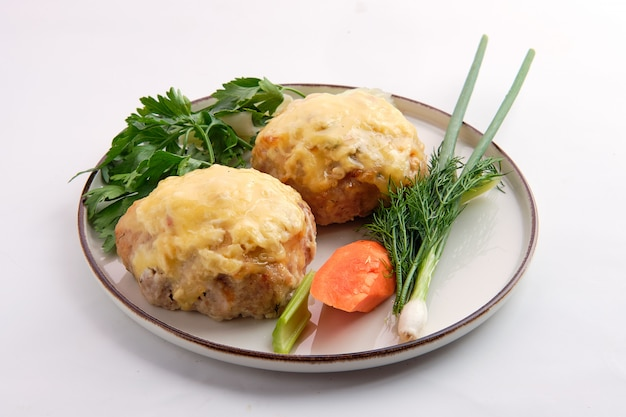 Mit geschmolzenem käse überzogenes schnitzel, serviert mit frischer karotte, frühlingszwiebel und parmesan