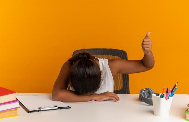 Mit gesenktem kopf sitzt junges schulmädchen am schreibtisch mit schulwerkzeugen, ihr daumen nach oben isoliert auf orange wand