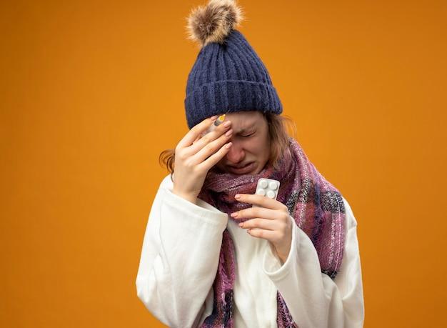 Mit gesenktem kopf weinendes junges krankes mädchen, das weißes gewand und wintermütze mit schal hält, der spritze mit pillen hält, die hand auf stirn lokalisiert auf orange setzen