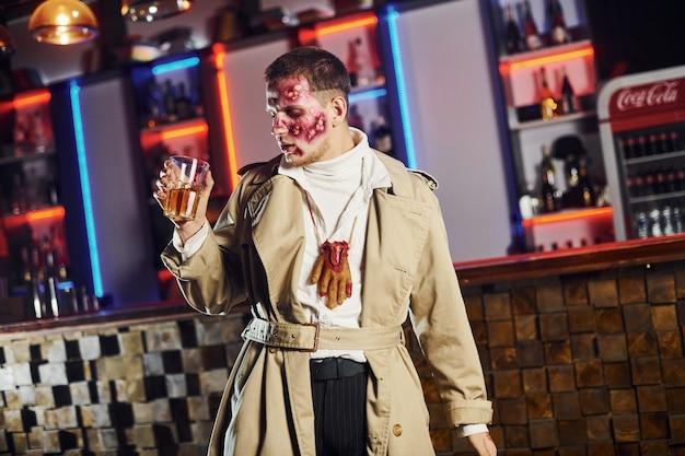 Mit getränk in der hand. porträt des mannes, der auf der thematischen halloween-party in zombie-make-up und -kostüm ist.