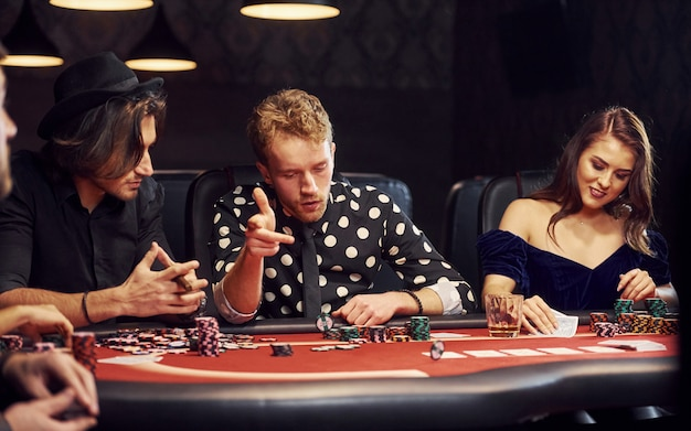 Mit gläsern zu trinken. gruppe elegante junge leute die, die zusammen poker im kasino spielen