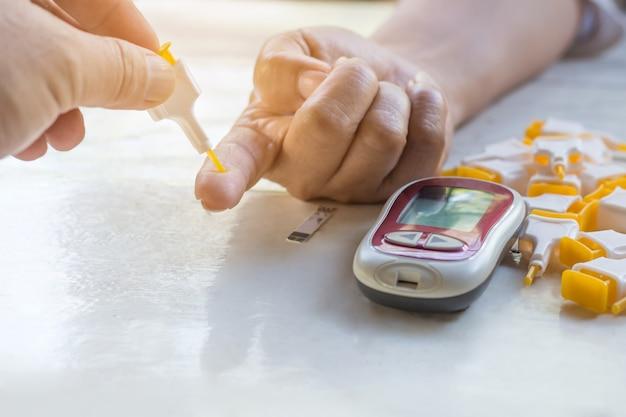 Mit glucometer zu hause und zubehör wird der blutzuckerspiegel kontrolliert