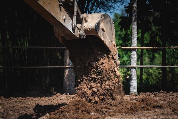 Mit großen maschinen den boden graben bagger arbeiten daran, den boden zu graben, einen teich zu graben oder eine große infrastruktur aufzubauen. bodenarbeiten und öffentliche arbeiten