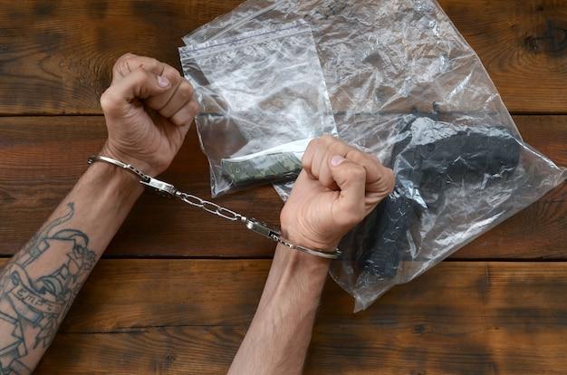 Mit handschellen gefesselte hände eines kriminellen verdächtigen auf holztisch und pistole mit klappmesser in transparenten plastikverpackungen als tatortbeweis für ermittlungen