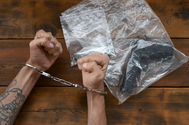 Mit handschellen gefesselte hände eines kriminellen verdächtigen auf holztisch und pistole mit klappmesser in transparenten plastikverpackungen