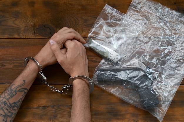Mit handschellen gefesselte hände eines kriminellen verdächtigen auf holztisch und pistole mit klappmesser