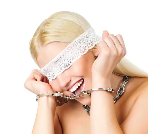 Mit handschellen gefesselte nackte blonde frau mit weißem spitzenverband zum schließen der augen und mit ketten um den hals. auf lichtwand isoliert