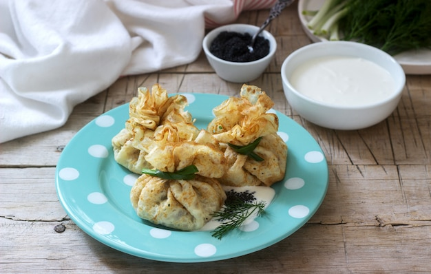 Mit hering gefüllte pfannkuchensäcke, serviert mit kaviar, sauerrahm und dill auf holzhintergrund. rustikaler stil.