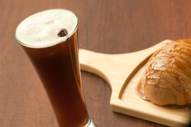 Mit honig beträufeltes brot auf einem holzteller und ein glas cocktail mit beeren