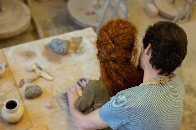 Mit intensiver meisterklasse. romantisches junges paar, das sich während eines ungewöhnlichen hobbys in der werkstatt leidenschaftlich umarmt
