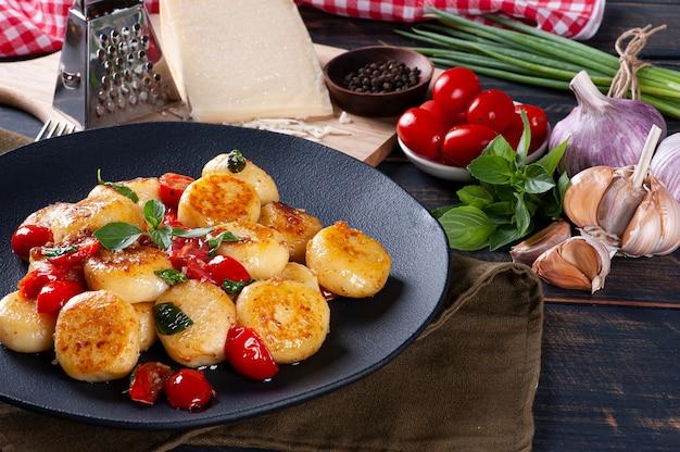 Mit käse gefüllte handwerkliche gnocchi mit kirschtomaten, knoblauch, olivenöl und basilikum