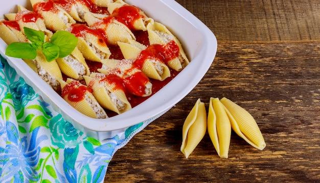Mit käse und champignons gefüllte muschelnudeln, mit parmesankäse bestreut.