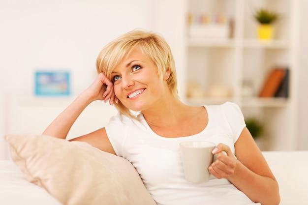 Mit kaffee auf der couch ausruhen