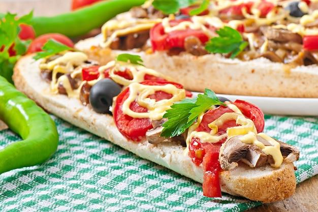 Mit kalbfleisch und pilzen gefülltes baguette mit tomaten und käse