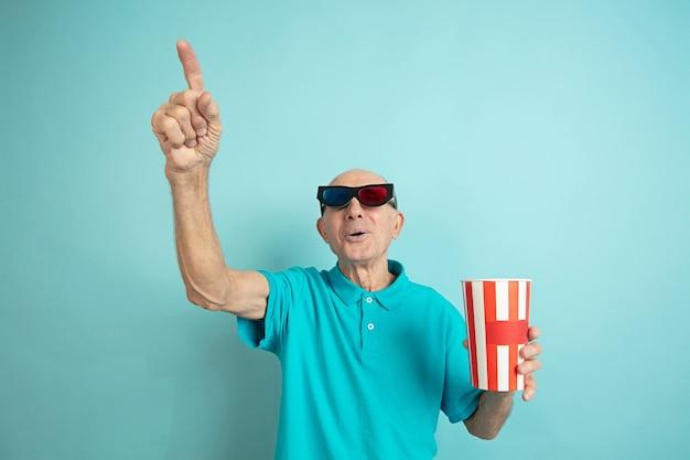 Mit kinobrillen nach oben zeigen. porträt des kaukasischen älteren mannes auf blauem studio.