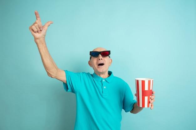 Mit kinobrillen nach oben zeigen. porträt des kaukasischen älteren mannes auf blauem studiohintergrund. schönes emotionales modell. konzept der menschlichen emotionen, gesichtsausdruck, verkauf, wohlbefinden, anzeige. copyspace.