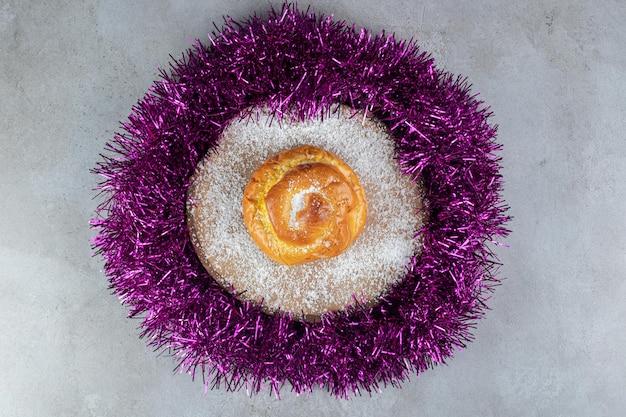 Mit kokosnusspulver bedeckter untersetzer mit einem brötchen in einem girlandenkreis auf marmoroberfläche