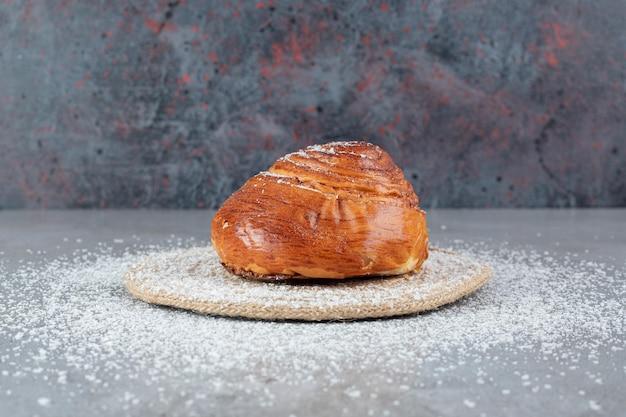 Mit kokosnusspulver bedeckter untersetzer unter einem süßen brötchen auf marmoroberfläche