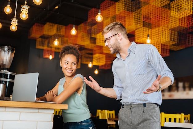 Mit kollegen sprechen. blondhaariger stilvoller mann, der brille trägt, die mit seinem kollegen spricht, der mit laptop arbeitet
