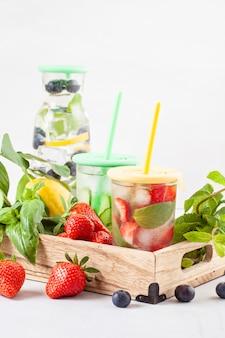 Mit kräutern und früchten aromatisiertes wasser. sommerliches erfrischungsgetränk. gesundheitswesen, eignung, gesundes nahrungsdiätkonzept.
